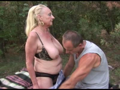 Blonde geile GILF Fotze mit großen Titten und rasierter Spalte fickt im Wald mit jungem Stecher