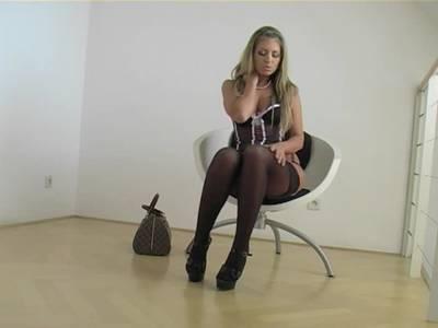 Heißes Girl in schwarzen Dessous strippt auf einem Stuhl sitzend